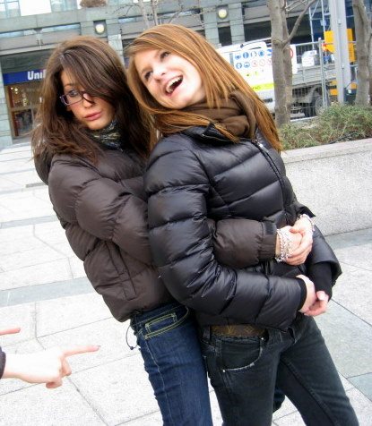 Two Girls In Down Jackets Hugging Shiny Nylon